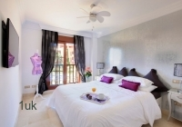 Bedroom two in white and purple
