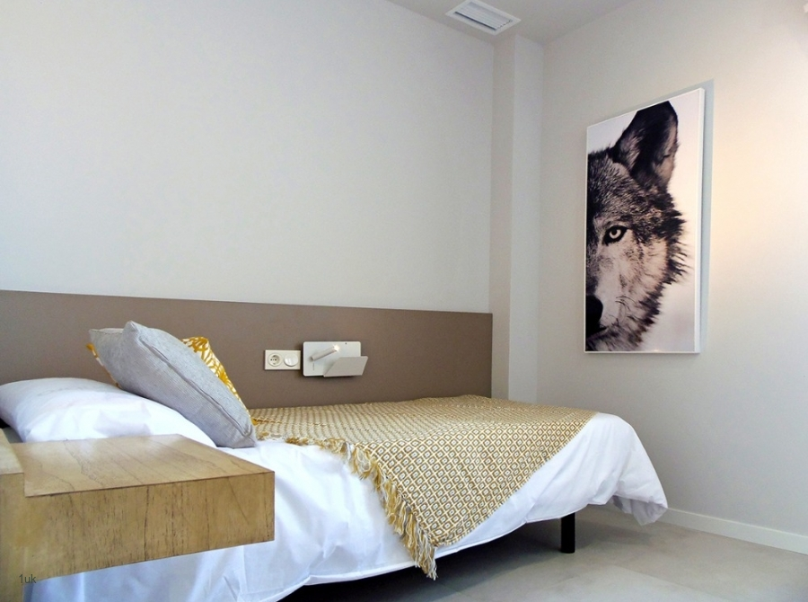 Bed with electric sockets and picture on the wall