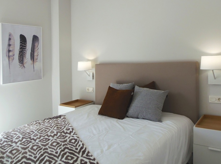 White washed walls with double bed and cabinets