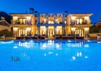 The villa and pool lit up at night