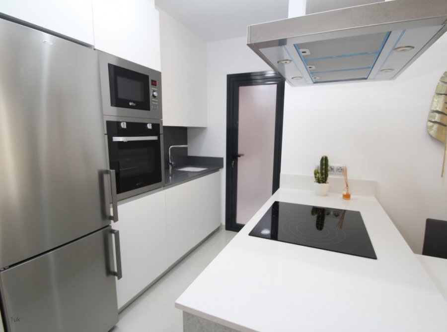 White washed kitchen area with cooker, microwave and fridge