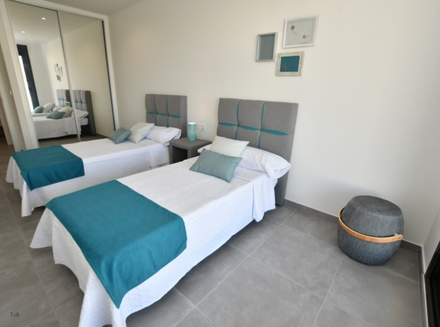 Two single beds in room with mirror cupboards