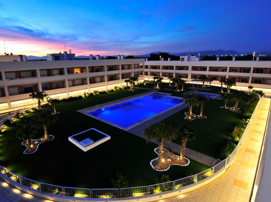 Night time birdseye view of apartments and swimming pool