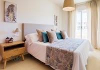 Master bedroom with large sliding windows and bedside cabinets