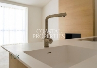 White kitchen sink with stainless steel hot and cold tap