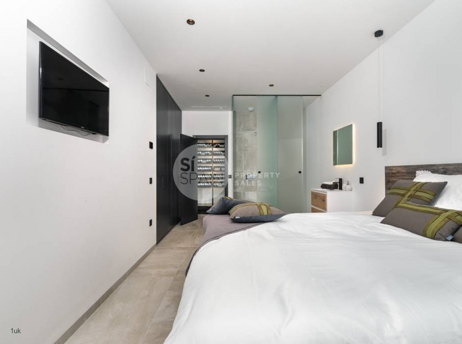 White washed bedroom with modern TV