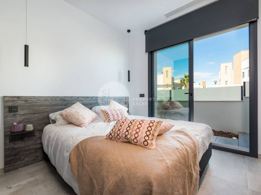 Guest bedroom with sliding glass doors and electric blinds