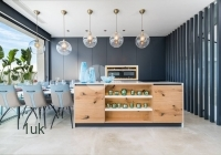 Open plan kitchen with wooden center piece and dining table