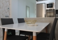 Four black chairs around square white dining table